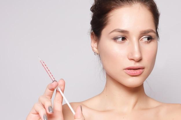 Mulher jovem e atraente obtém injeção cosmética, isolada sobre fundo branco. mão feminina segura uma seringa para injeção perto do rosto. tratamento de beleza.