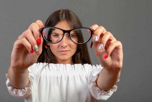 Mulher jovem e atraente, olhando através de óculos. isolado em cinza