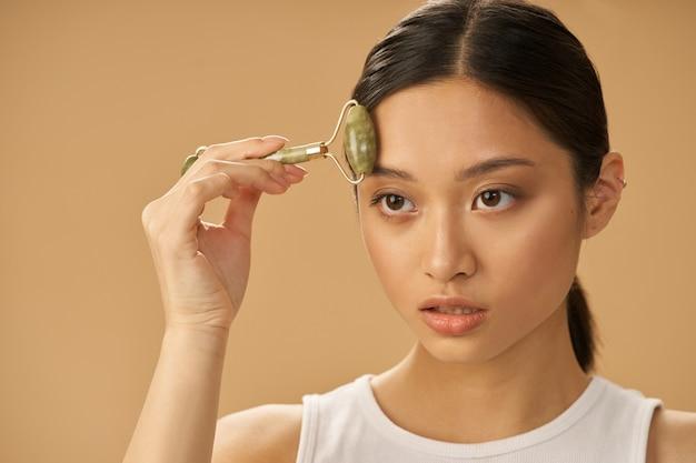 Mulher jovem e atraente olhando para o lado enquanto usa o rolo de jade para massagear o rosto