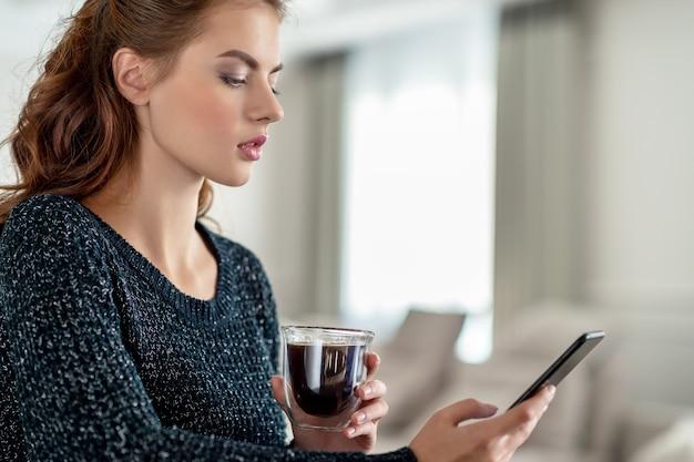 Mulher jovem e atraente olhando para seu telefone inteligente em casa. mulher digita mensagem em seu telefone inteligente.