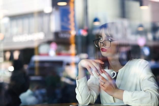 Mulher jovem e atraente passando um tempo no restaurante com uma xícara de café, vista através do vidro