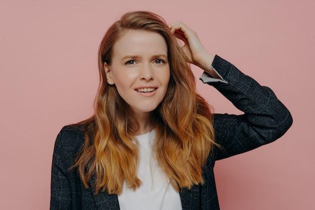 Mulher jovem e atraente pensativa com cabelo ruivo ondulado em jaqueta escura formal e top branco pensando enquanto toca a cabeça com confusão em pé contra o fundo rosa do estúdio