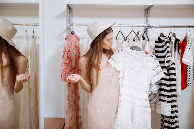 Mulher jovem e atraente pensativa em pé e escolhendo um vestido em uma loja de roupas