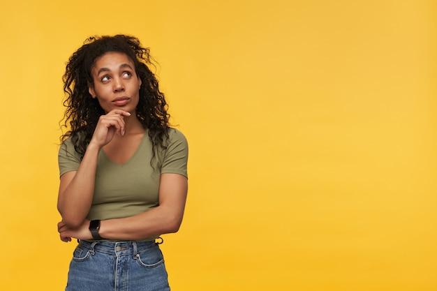 Mulher jovem e atraente pensativa em roupas casuais, pensando e desviando o olhar para o lado na copyspace isolada sobre a parede amarela