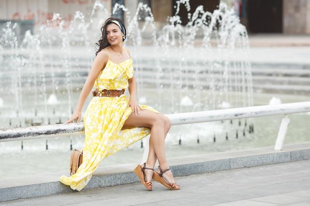 Mulher jovem e atraente perto da fonte. linda mulher ao ar livre. senhora no retrato de vestido amarelo.