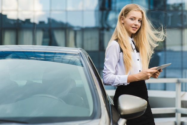 Mulher jovem e atraente perto de carro mantém tablet