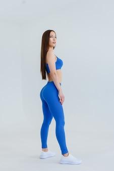 Mulher jovem e atraente posando com um agasalho azul. fitness, estilo de vida saudável.