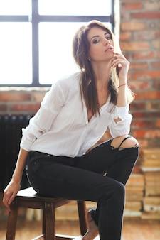 Mulher jovem e atraente posando com uma camisa branca e calça jeans