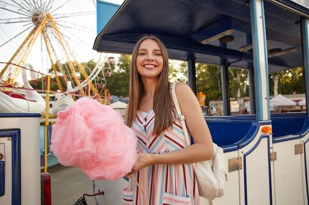 Mulher jovem e atraente, positiva, morena, com cabelo comprido posando sobre um parque de diversões em um dia quente de sol, usando um vestido romântico e uma mochila, segurando um bastão com algodão doce rosa
