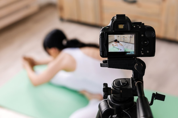 Mulher jovem e atraente praticando ioga e tiro de vídeo