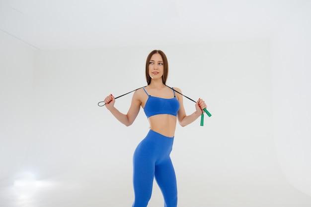 Mulher jovem e atraente pulando corda em um agasalho azul. fitness, estilo de vida saudável.