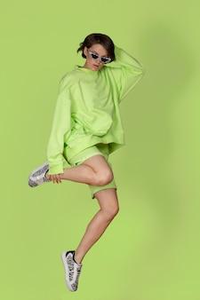 Mulher jovem e atraente pulando em um terno esportivo verde sobre o fundo verde