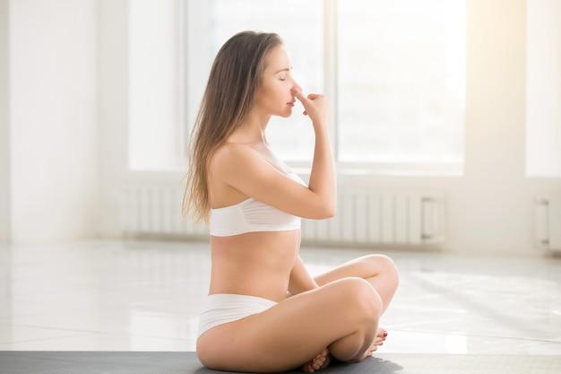 Mulher jovem e atraente que faz respiração alternativa de nostril, branca