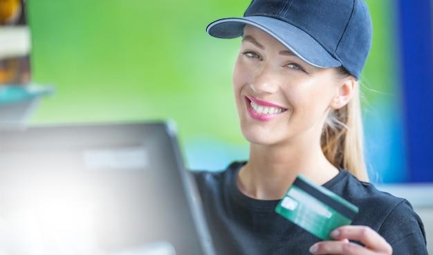 Mulher jovem e atraente que trabalha em um balcão de dinheiro com um cartão de crédito.