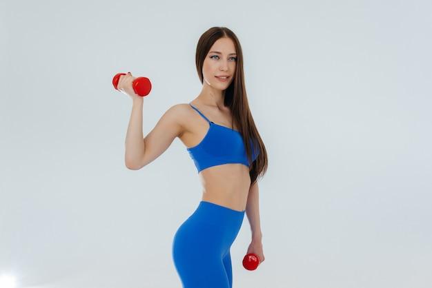 Mulher jovem e atraente realiza exercícios de esportes. fitness, estilo de vida saudável.