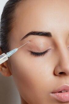 Mulher jovem e atraente recebendo injeção cosmética