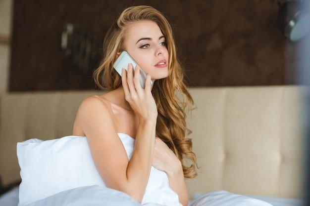 Mulher jovem e atraente relaxada sentada na cama falando ao celular