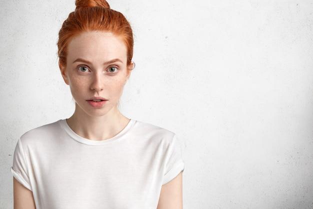Mulher jovem e atraente ruiva com expressão séria, pele sardenta, vestida casualmente, posa contra o espaço em branco