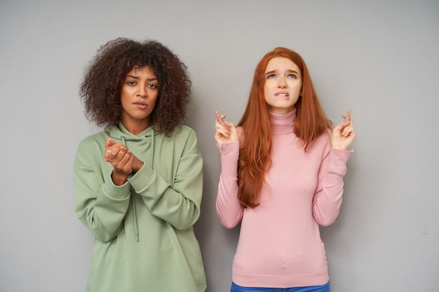 Mulher jovem e atraente ruiva de cabelos compridos ansiosa mordendo o lábio inferior e levantando os dedos cruzados enquanto fica de pé sobre uma parede cinza com uma esperançosa senhora morena de pele escura