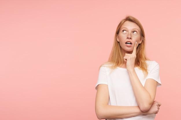 Mulher jovem e atraente ruiva perplexa segurando o dedo indicador na bochecha enquanto olha pensativamente para cima, vestida com roupa casual e de pé sobre um fundo rosa