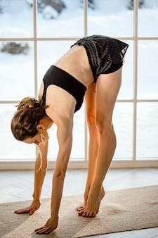Mulher jovem e atraente saudável com blusa preta esportiva e shorts fazendo ioga, alongamento em casa