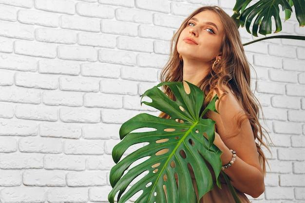 Mulher jovem e atraente se escondendo atrás de folha de monstera. foto criativa