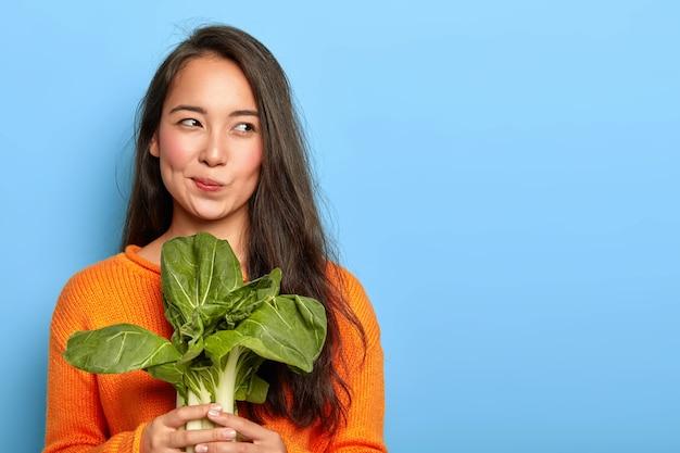 Mulher jovem e atraente segura vegetais verdes frescos, come comida saudável em casa, usa produtos alimentares para fazer salada vegetariana, usa suéter laranja, posa dentro de casa