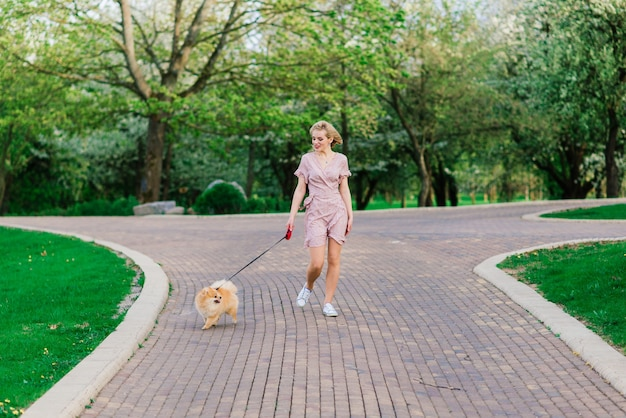 Mulher jovem e atraente segurando spitz de cachorro do lado de fora e sorrindo, caminhando no parque. conceito sobre amizade entre pessoas e animais.