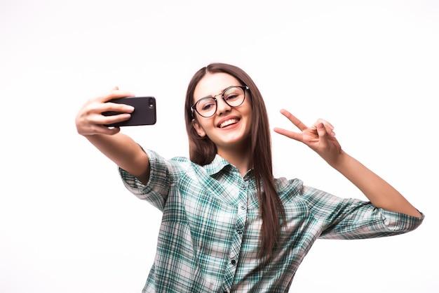Mulher jovem e atraente segurando um telefone celular e tirando uma foto de si mesma em pé contra o branco