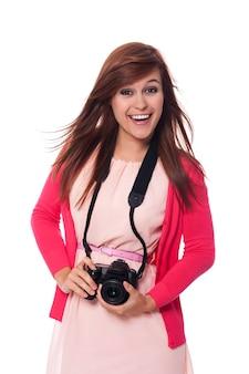Mulher jovem e atraente segurando uma câmera digital