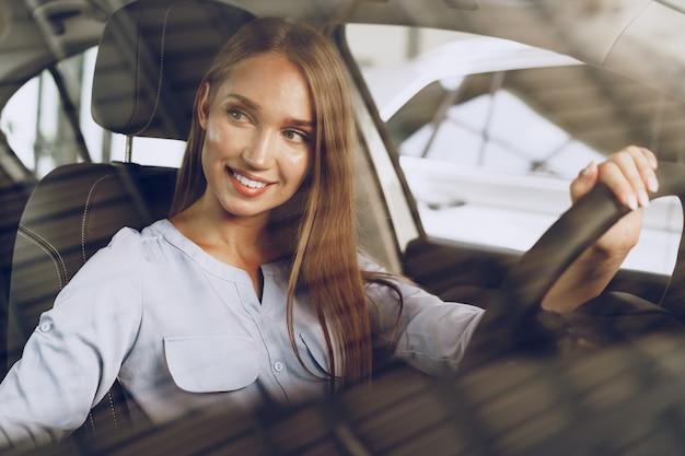 Mulher jovem e atraente sentada em um carro novo no showroom