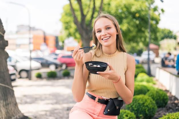 Mulher jovem e atraente sentada no banco comendo salada fresca e saudável