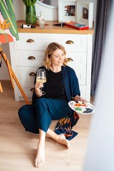 Mulher jovem e atraente sentada no chão, segurando a paleta de cores para pintar e beber vinho branco. artista feminina satisfeita comemorando seu trabalho acabado.