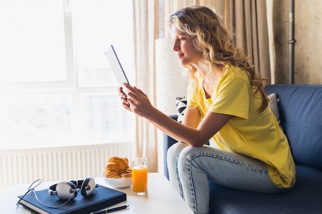 Mulher jovem e atraente sentada relaxada no sofá em casa segurando um tablet, assistindo online