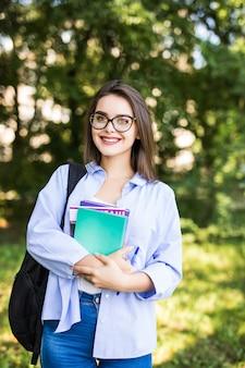 Mulher jovem e atraente sexy com livros em pé e sorrindo no parque