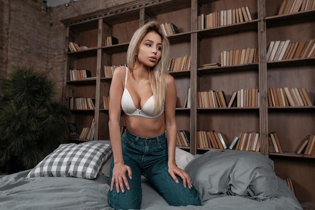 Mulher jovem e atraente sexy com seios lindos e corpo esguio em lingerie branca elegante e jeans da moda, sentada em uma cama dentro de casa