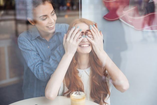 Mulher jovem e atraente sorridente cobrindo os olhos com as mãos da ruiva alegre