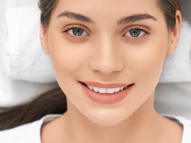 Mulher jovem e atraente sorridente com olhos azuis