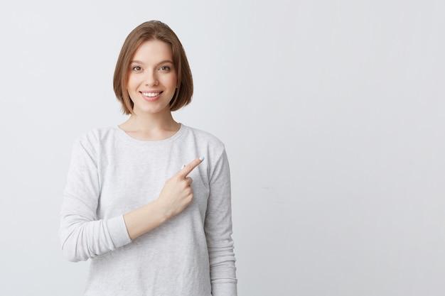 Mulher jovem e atraente sorridente de manga comprida em pé e apontando para o lado