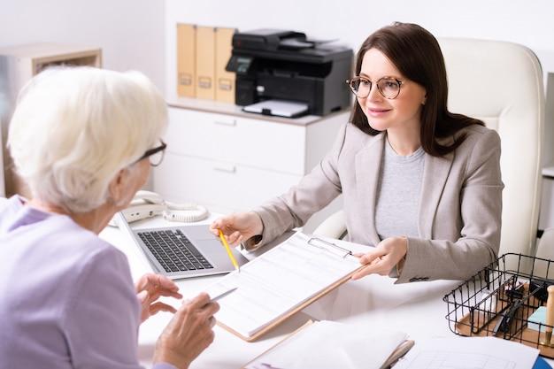 Mulher jovem e atraente sorridente de óculos, sentada na mesa e apontando para o papel, enquanto explica a senhora sênior como preencher o formulário