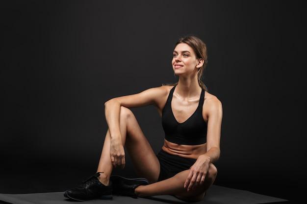 Mulher jovem e atraente, sorridente e saudável, vestindo sutiã esportivo e shorts isolados sobre um fundo preto, descansando em uma esteira de ginástica após se exercitar