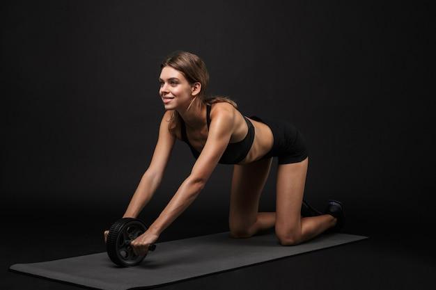 Mulher jovem e atraente sorridente fitness saudável usando sutiã esportivo e shorts isolados sobre um fundo preto, exercitando-se em uma esteira de fitness, usando roda ab