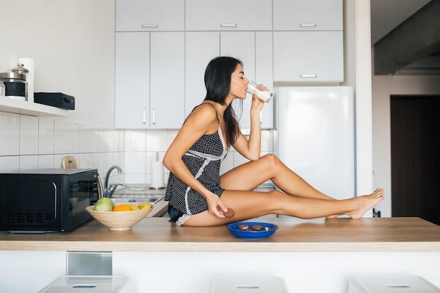 Mulher jovem e atraente sorridente se divertindo na cozinha pela manhã, tomando café da manhã, vestida com roupa de pijama, comendo biscoitos, bebendo leite, estilo de vida saudável, pernas longas e magras
