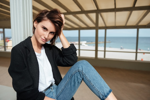 Mulher jovem e atraente sorridente, sentada em um caramanchão perto do mar