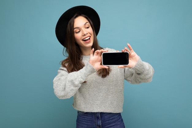 Mulher jovem e atraente sorridente usando chapéu preto e suéter cinza segurando um smartphone