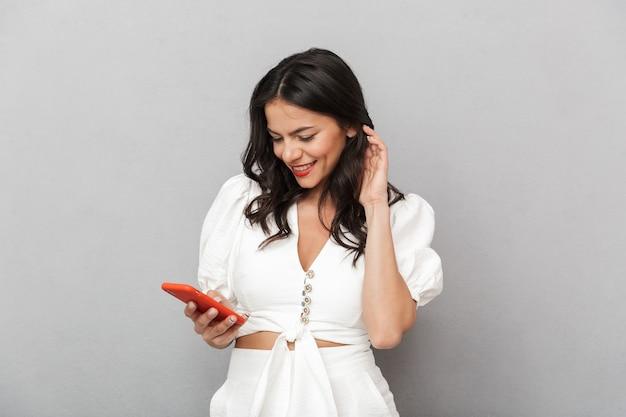 Mulher jovem e atraente sorridente, vestindo uma roupa de verão, em pé, isolada sobre uma parede cinza, usando um telefone celular