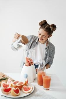Mulher jovem e atraente sorrindo adicionando água no liquidificador com pedaços de toranja e alecrim. nutrição alimentar de dieta saudável.