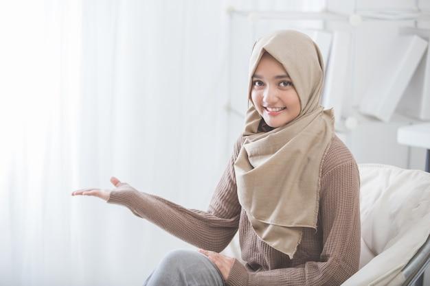 Mulher jovem e atraente sorrindo apresentando para copiar o espaço