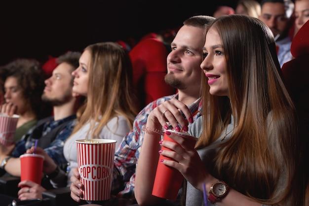 Mulher jovem e atraente sorrindo e abraçando o namorado enquanto assistem a um filme juntos no cinema