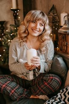 Mulher jovem e atraente sorrindo enquanto segura uma vela para celebrar o natal. ano novo - interior aconchegante